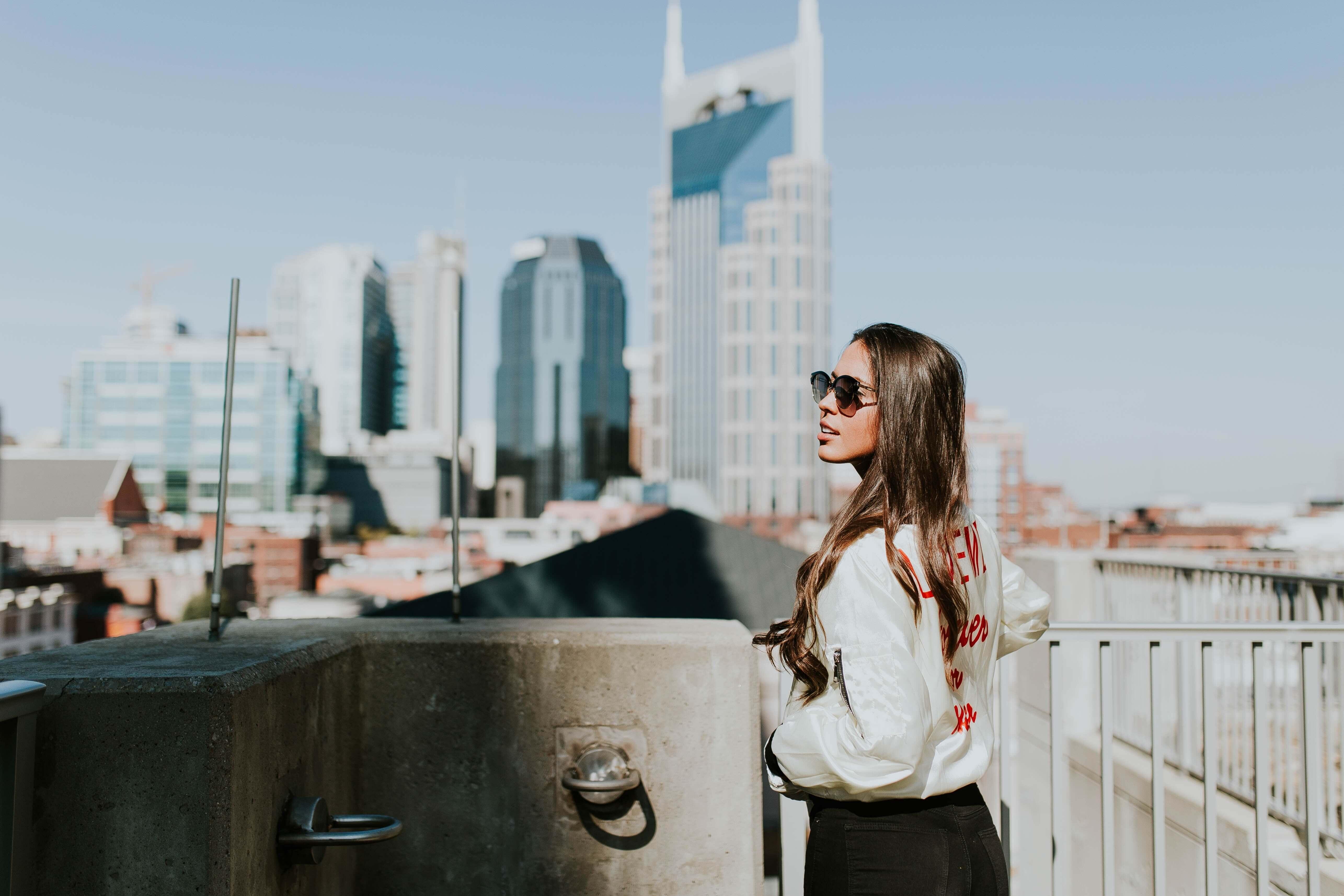 街を眺めるサングラスの女性