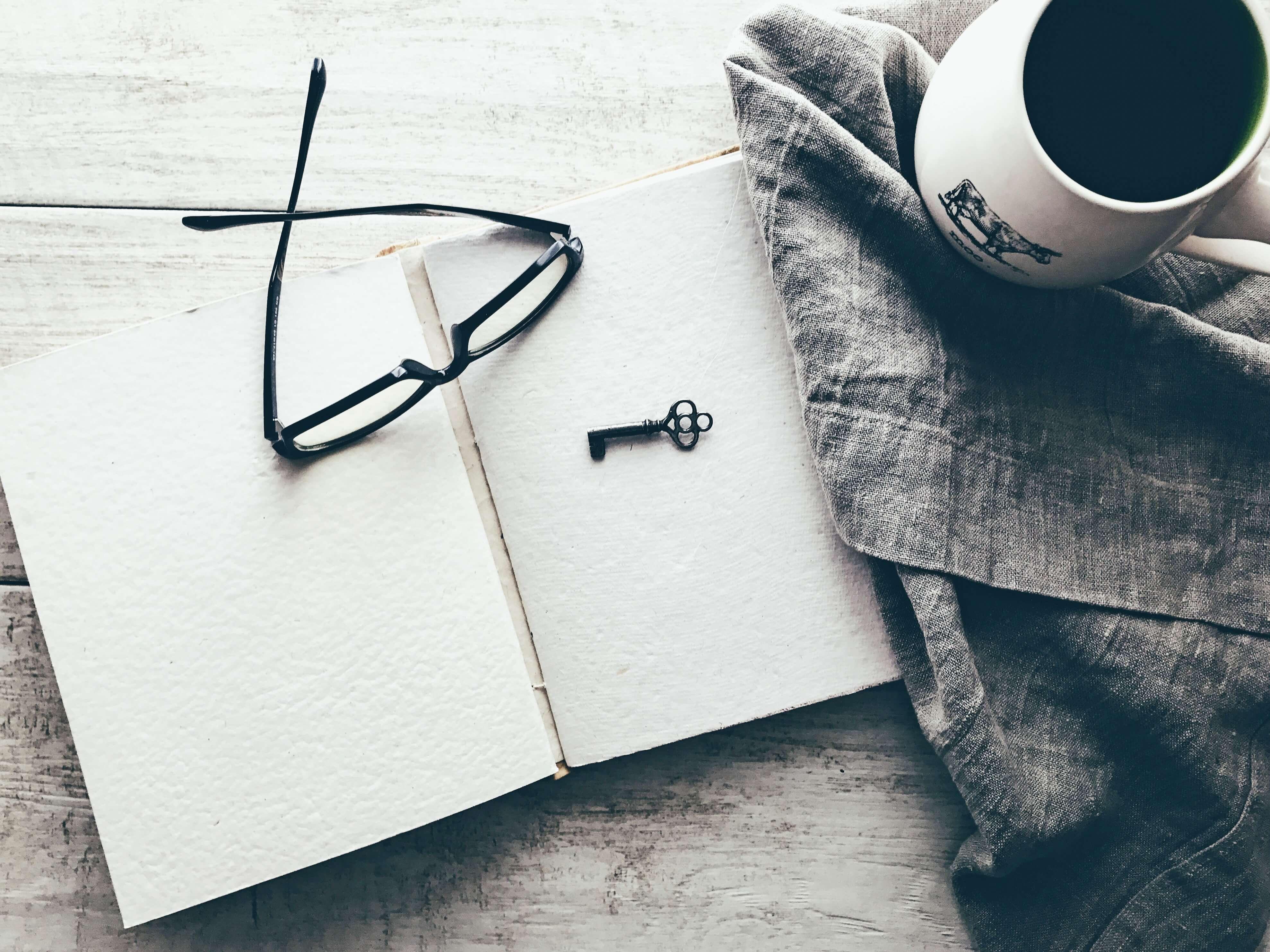 ノートの上に置かれたメガネと布の上に置かれたマグカップ