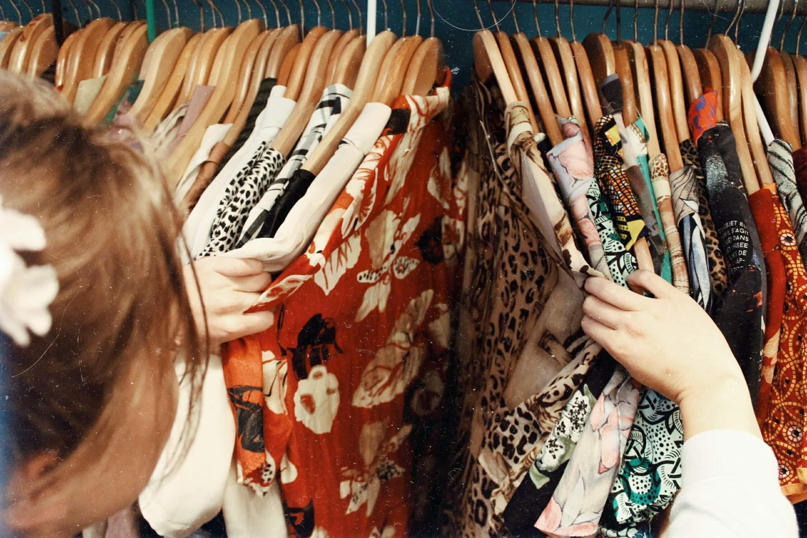 たくさんの服をかき分ける女性