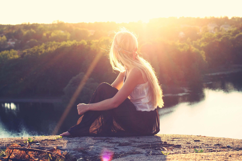 丘に座って夕日を見る女性