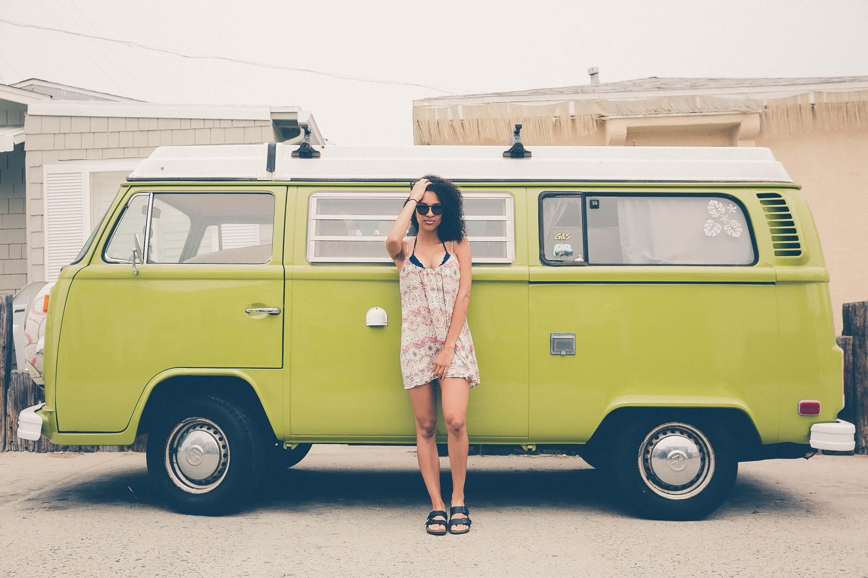 緑の車の前に立つ女性