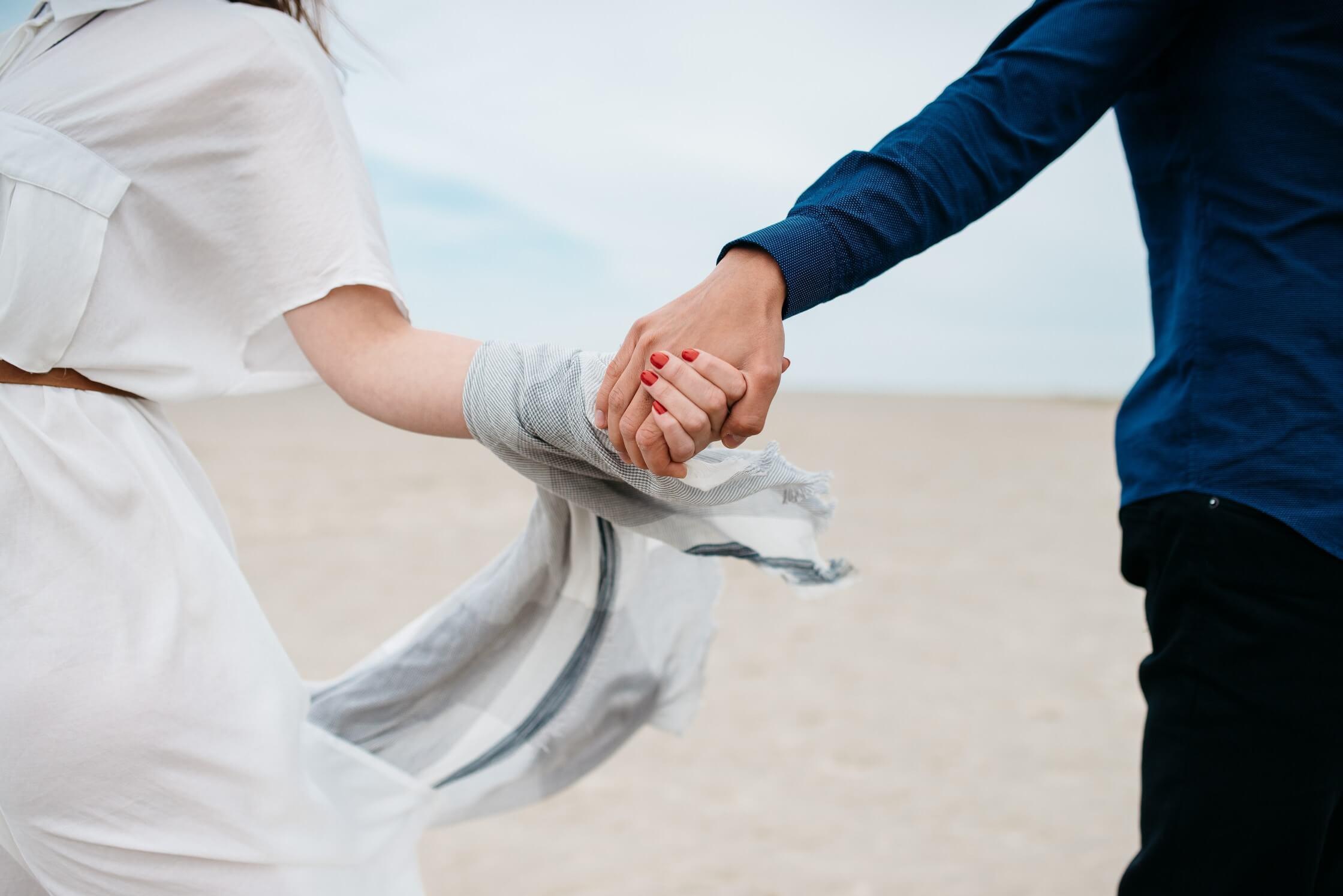 砂浜で手をつなぐ男女