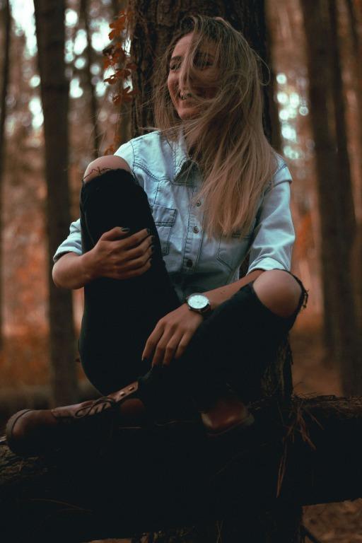 林の中に座る笑顔の女性