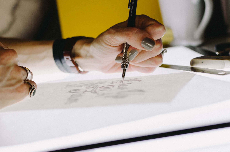紙にイラストを描く女性の手元