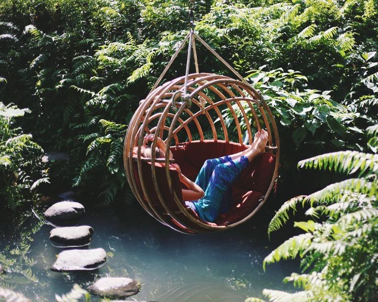 水辺に吊るされたリラックスチェアに座る女性