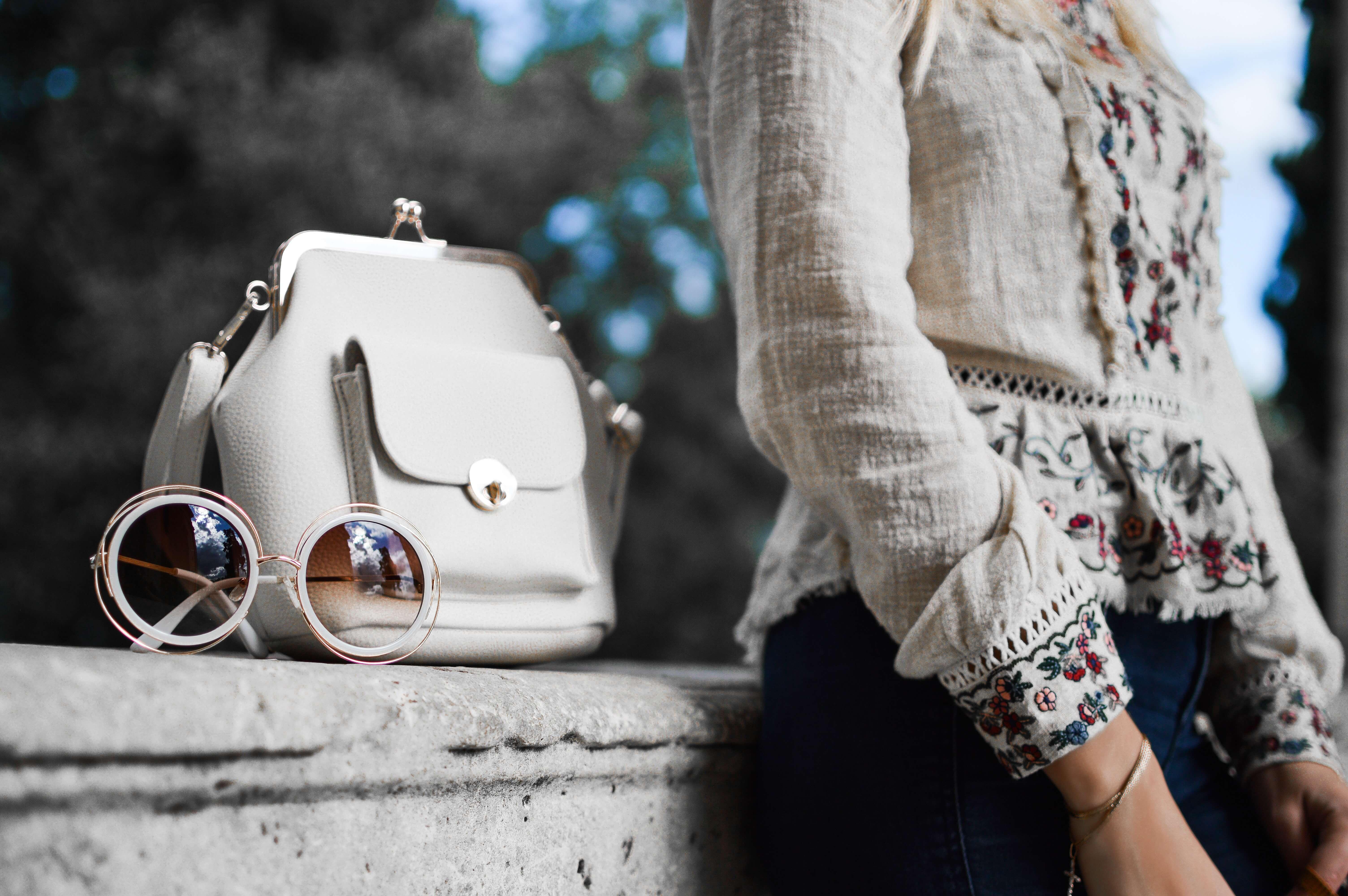 壁にもたれて立つ女性と横に置かれたベージュのバッグ