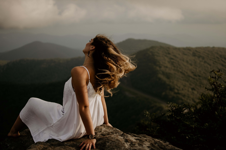 山中の岩の上に座る白いワンピースを着た女性