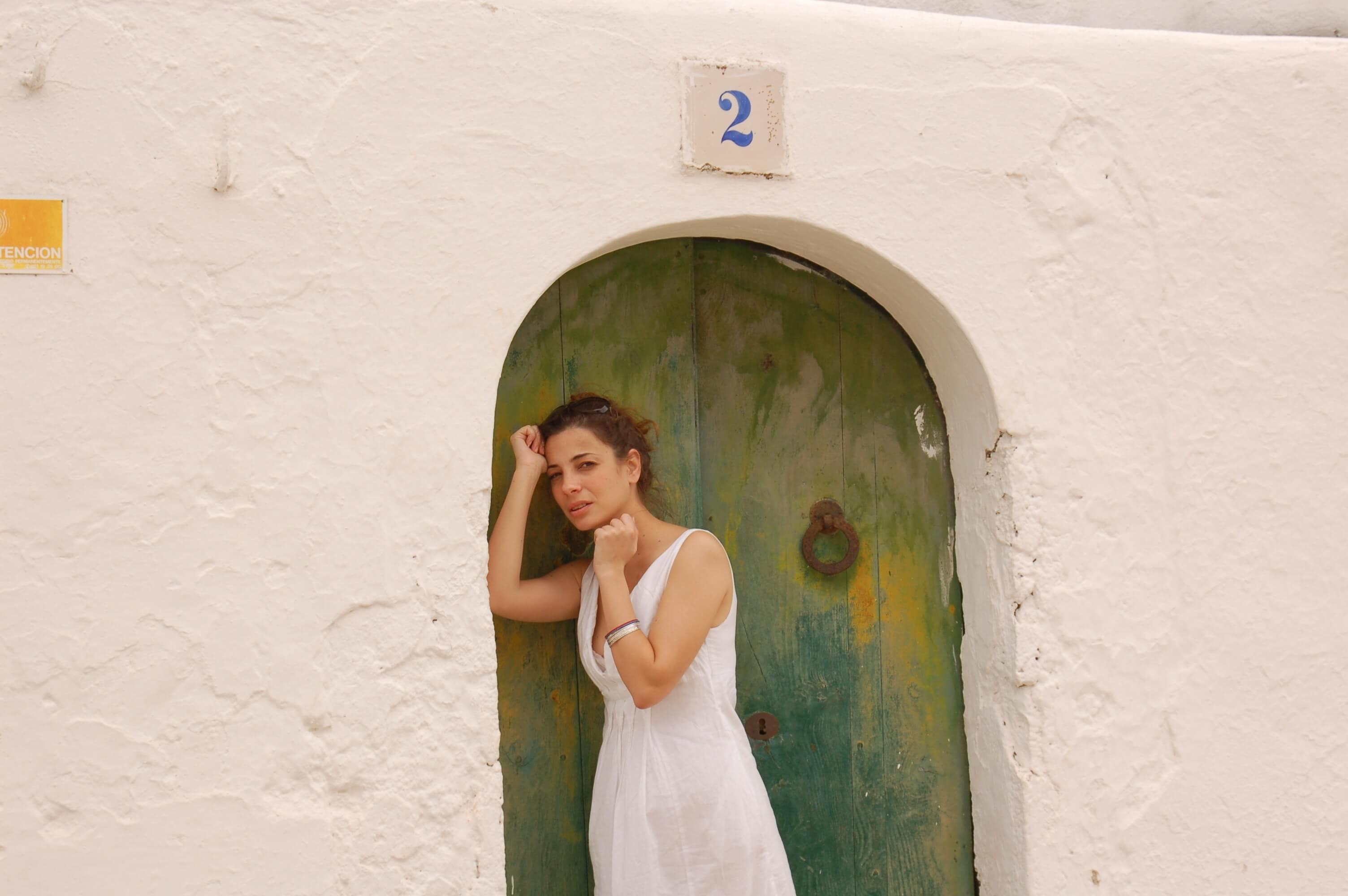 緑の扉の前に立つ女性