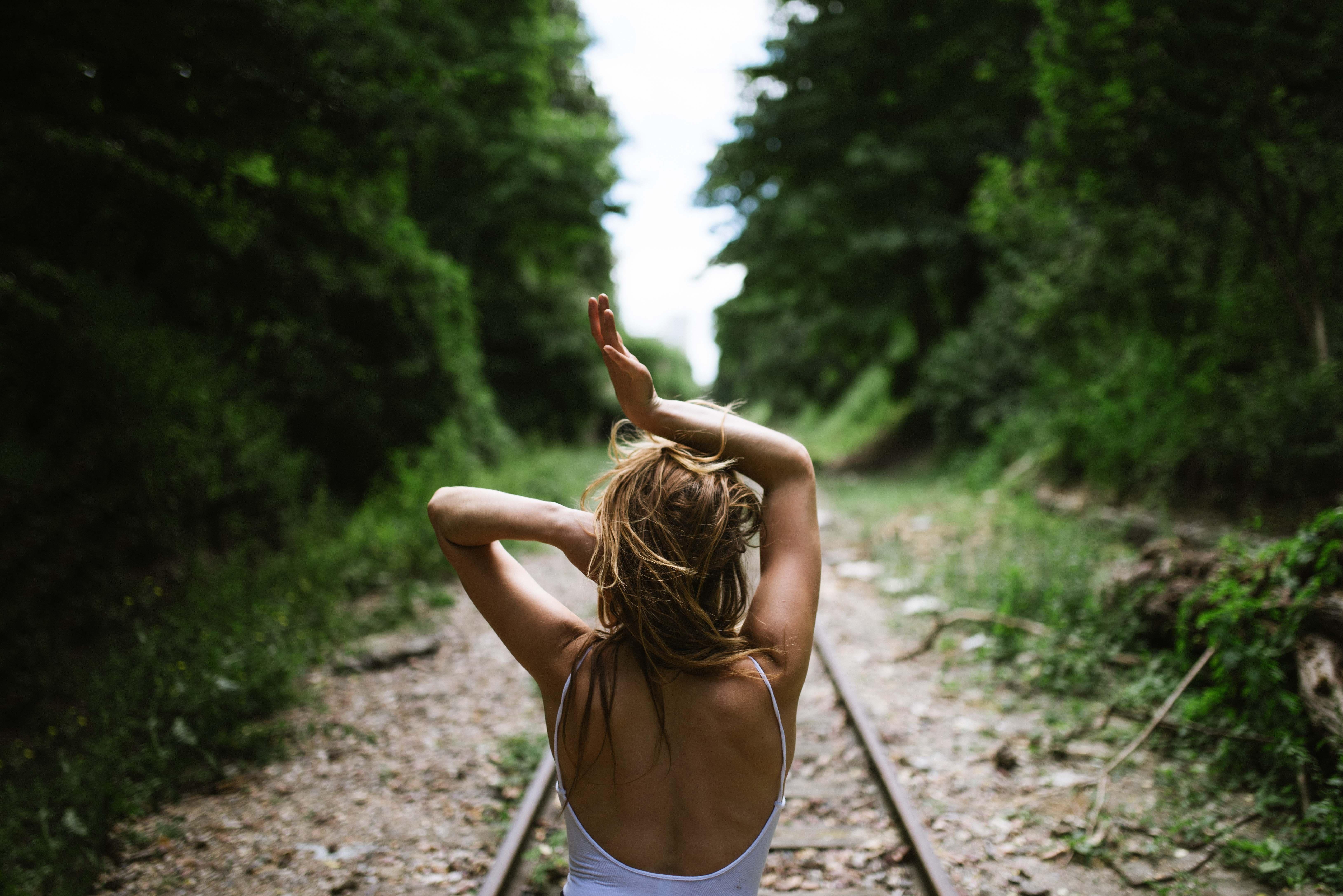 線路の上に立つ女性の後ろ姿