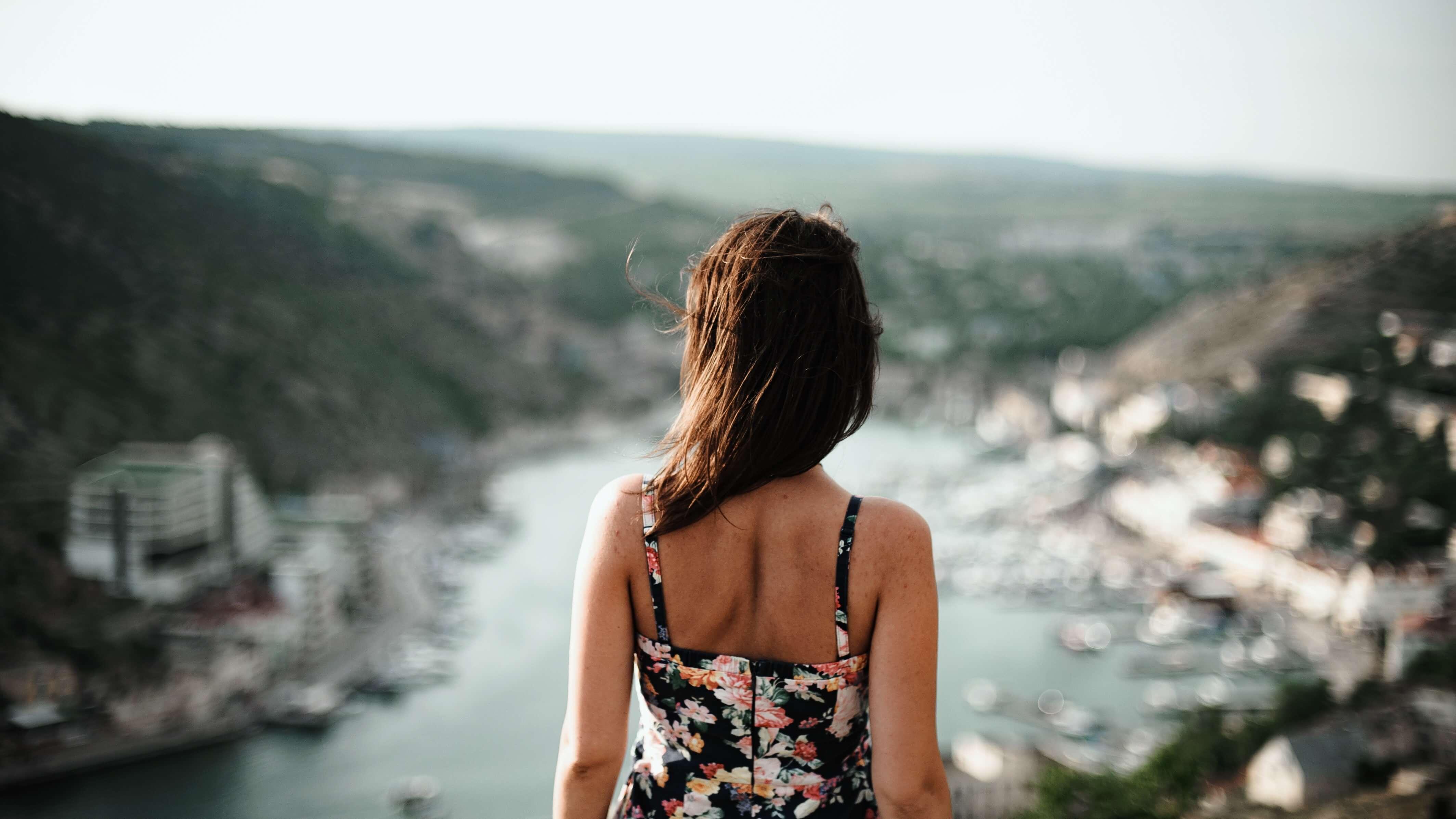 川を見下ろす花柄のワンピースの女性の後ろ姿