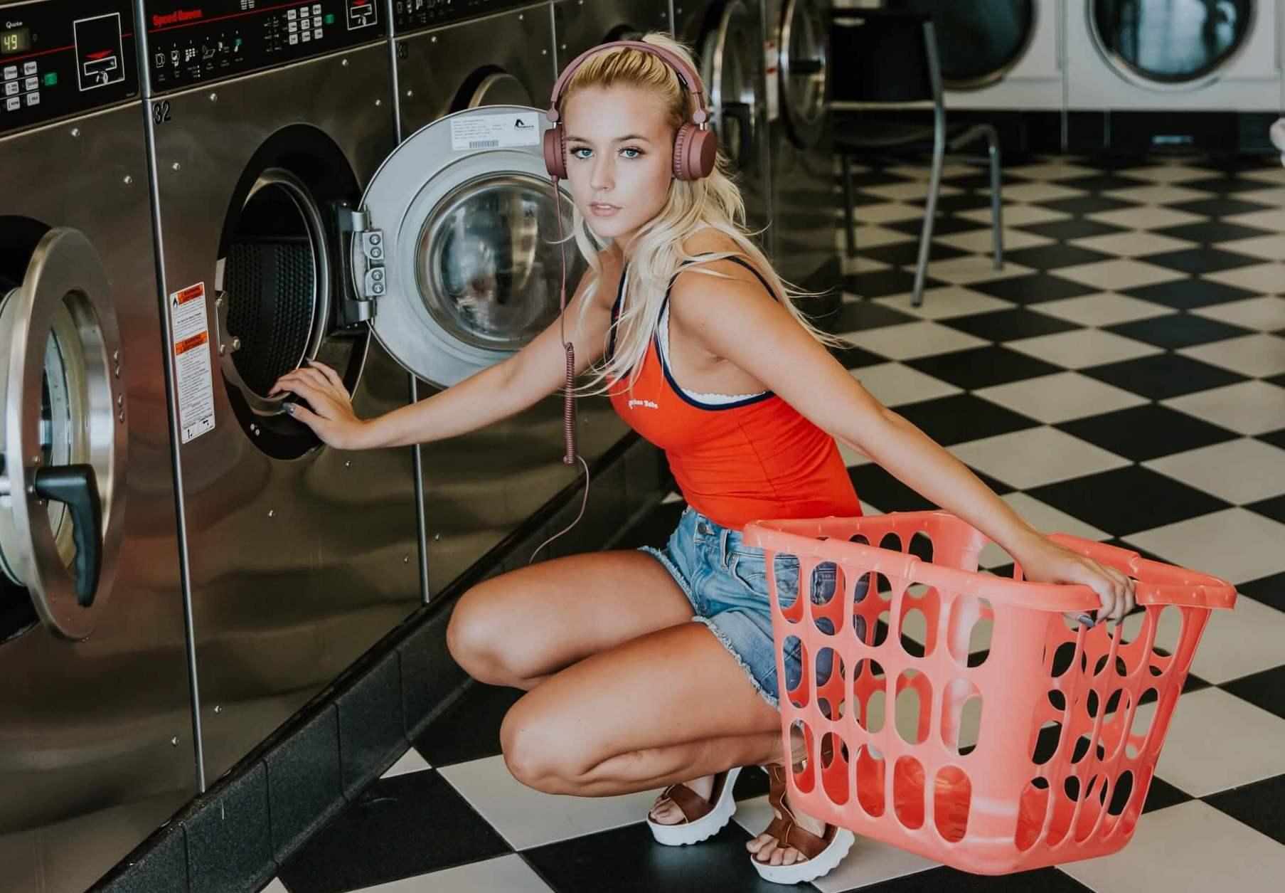 コインランドリーで洗濯カゴを持ってしゃがむ女性