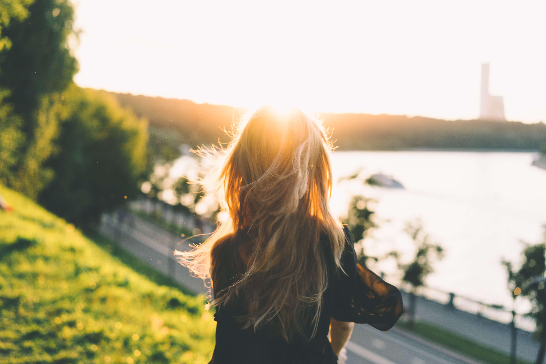 菜の花畑で夕日を眺める女性の後ろ姿