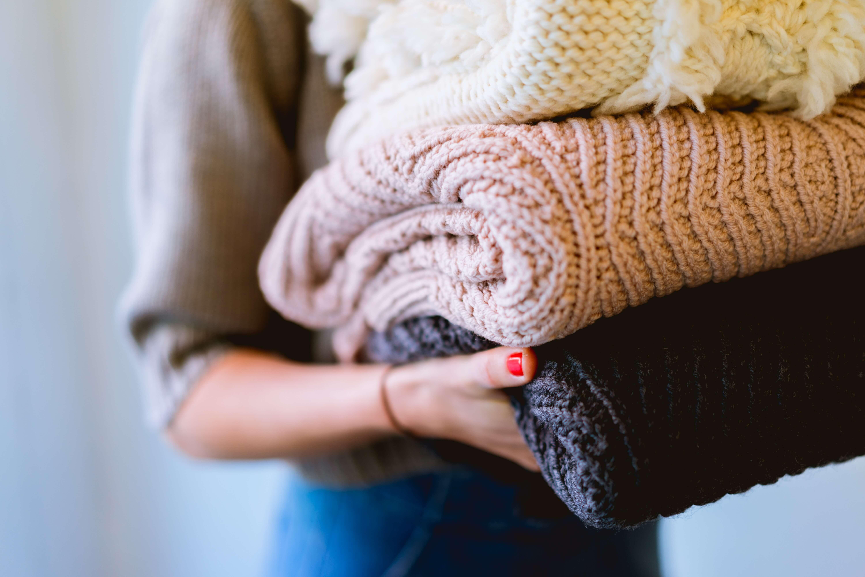 三着の畳んだセーターを手に持つ女性