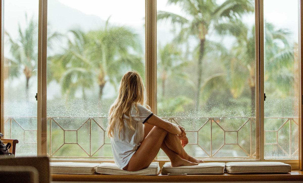 窓際に体育座りをして外の景色を眺める女性