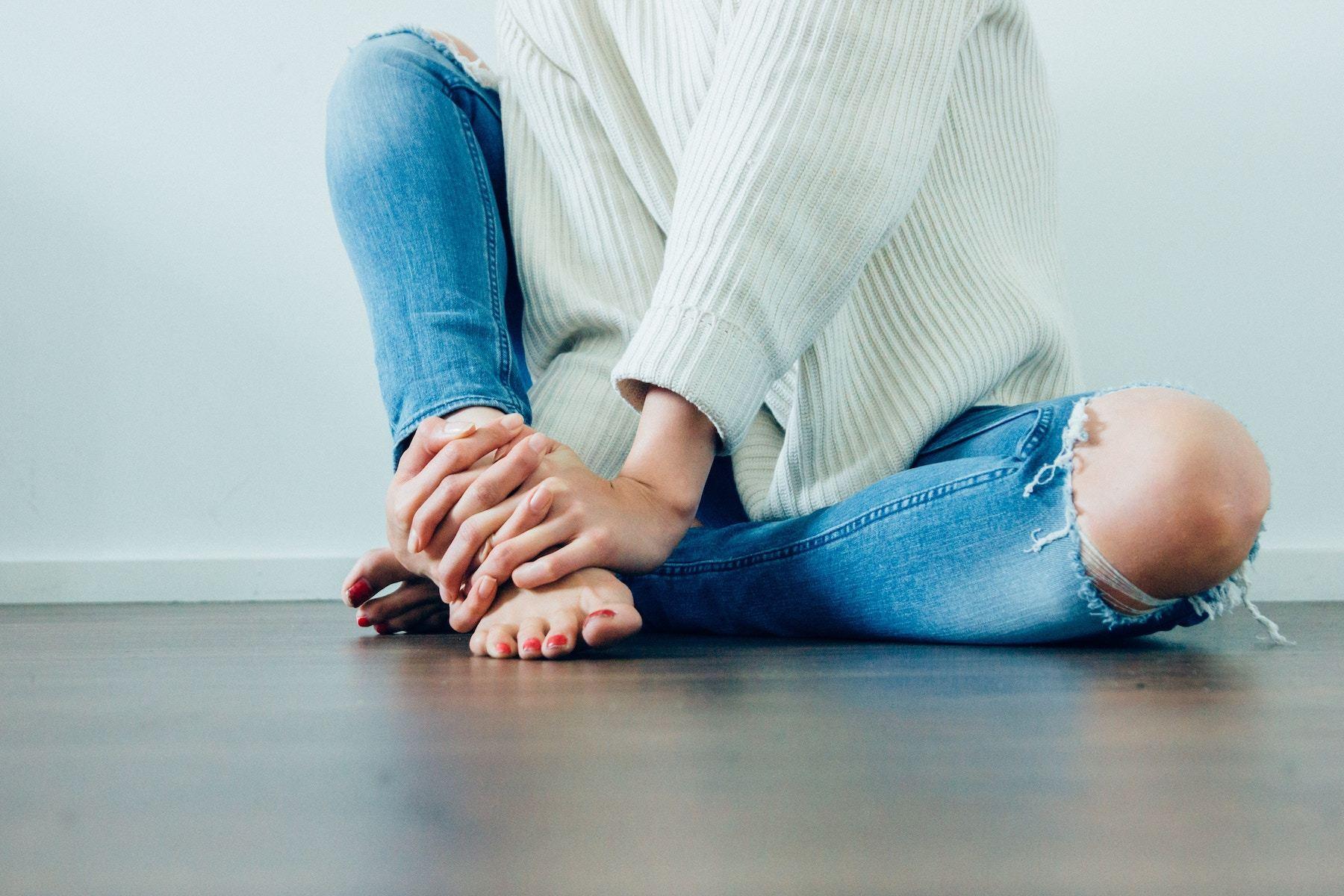 床に片膝を立てて座る女性