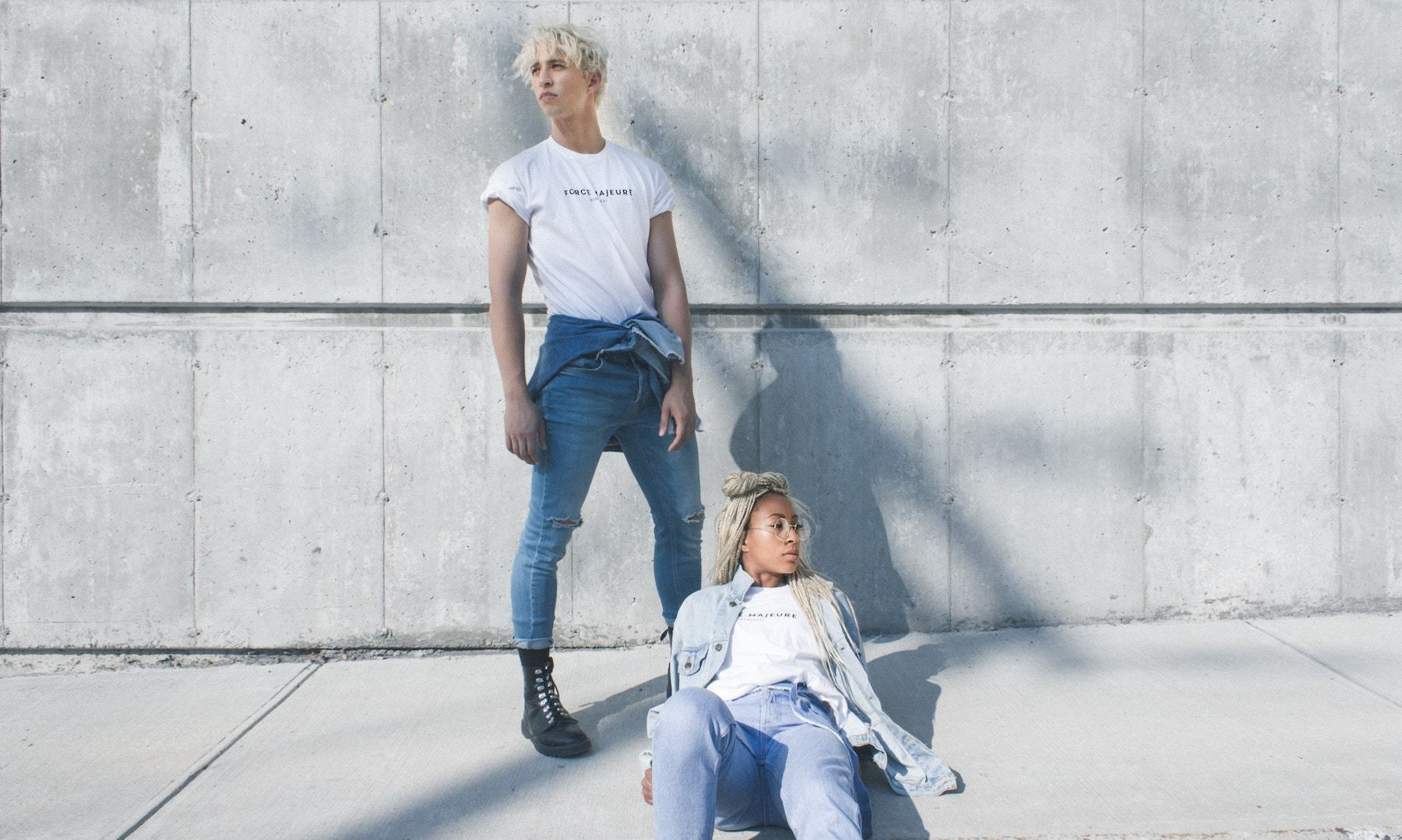 デニムを履いてコンクリートの壁の前に立つ男性と座る女性