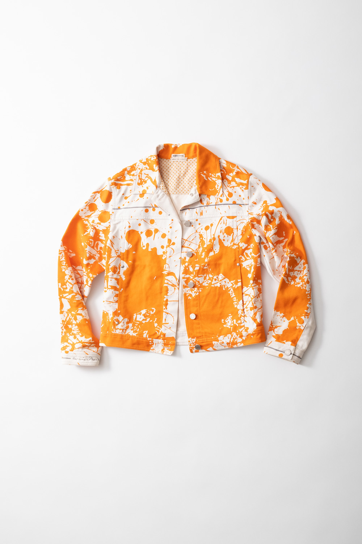 白地にオレンジのペイント柄のジャケット