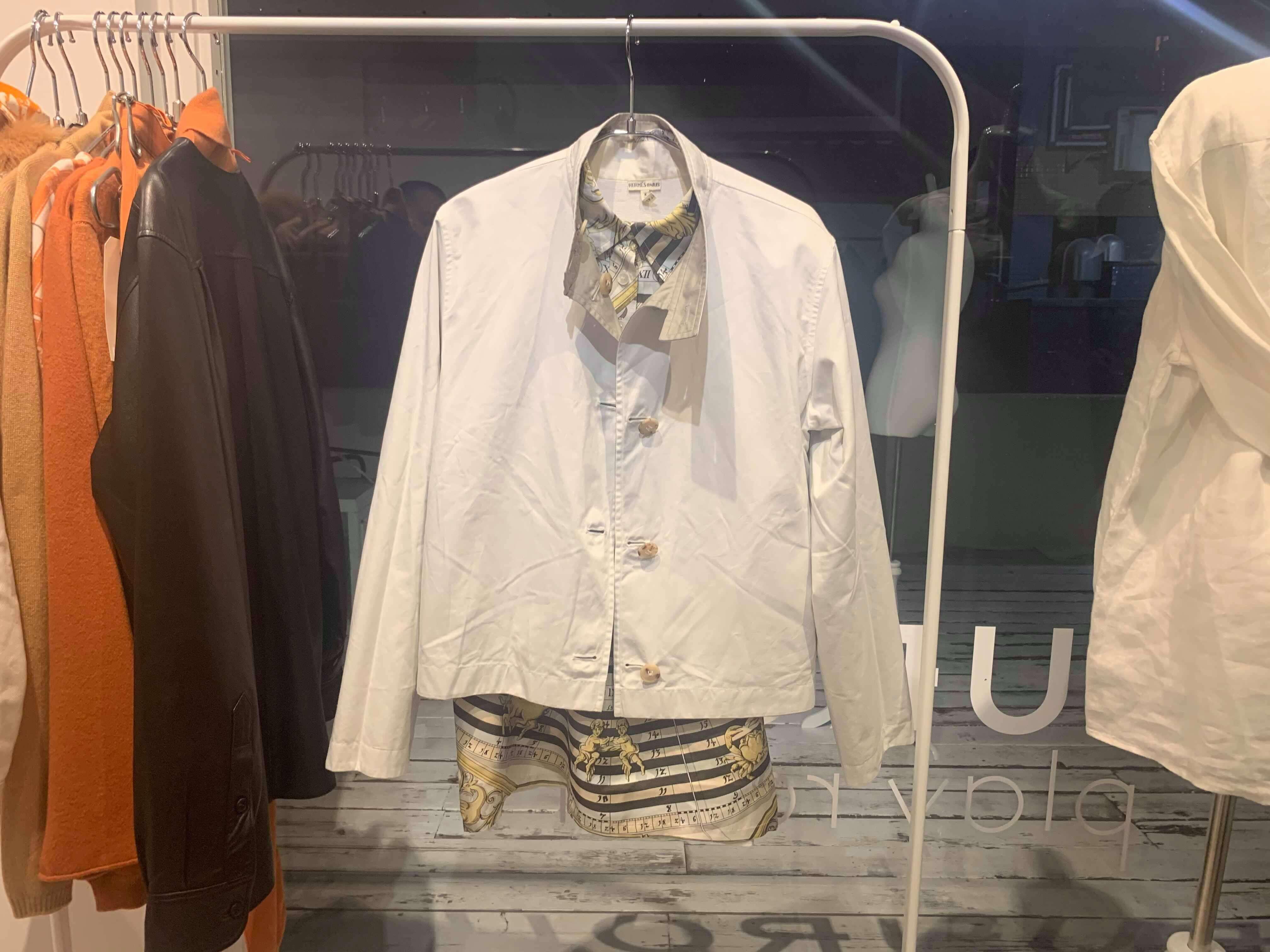 ハンガーラックにかかったエルメスの柄シャツと白いジャケット