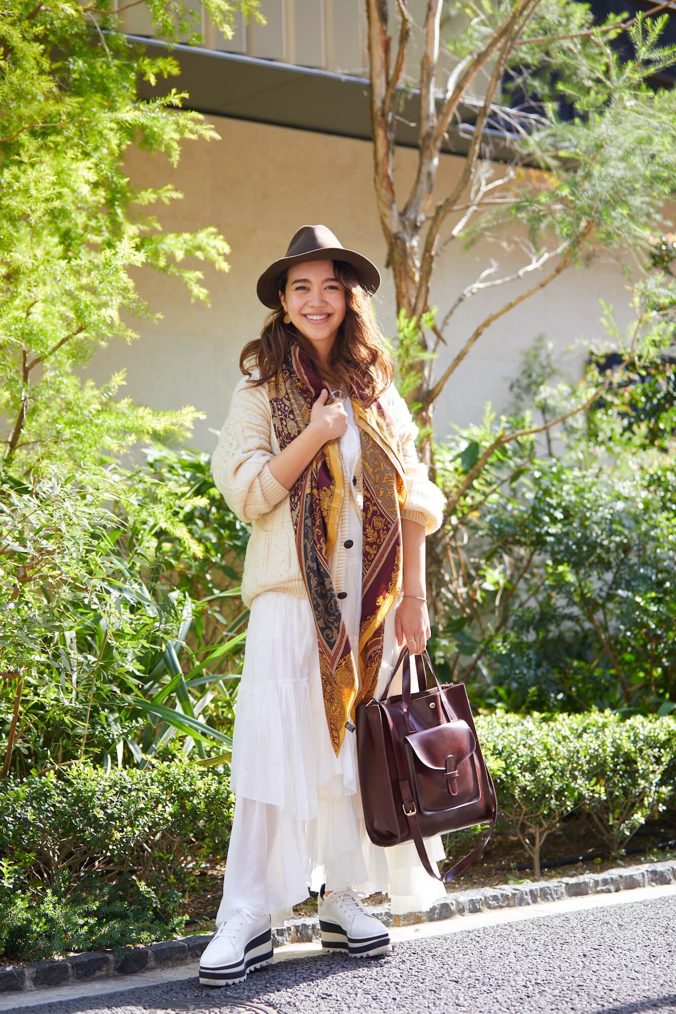 植え込みの前に立ち手にバッグを持ったエバンズ亜莉沙さん