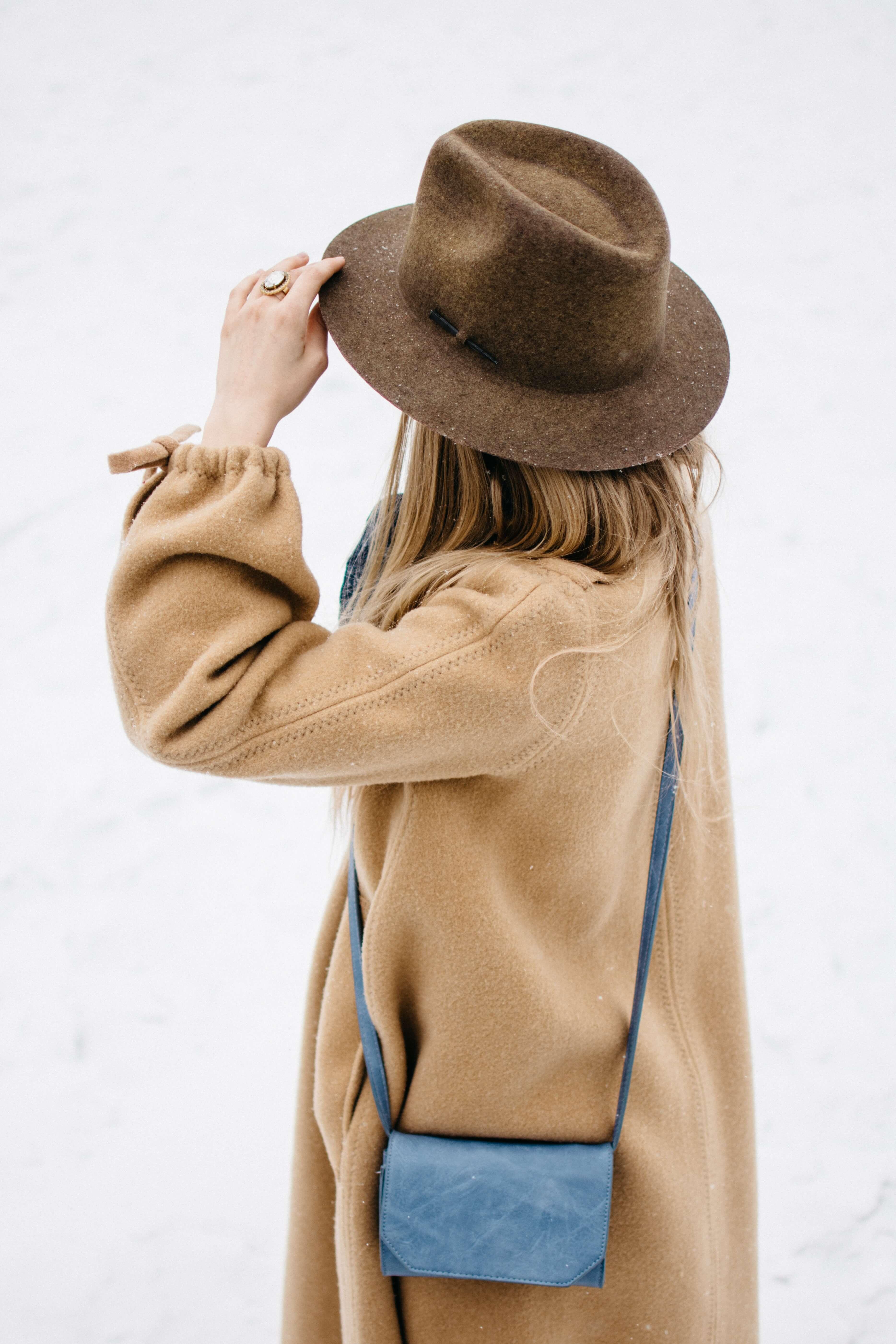 ベージュのコートでハットをかぶった女性