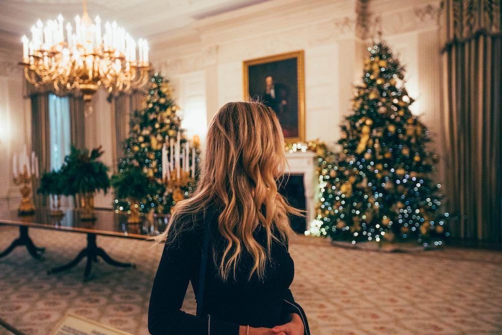 クリスマスの飾り付けをした部屋の中に立つ女性