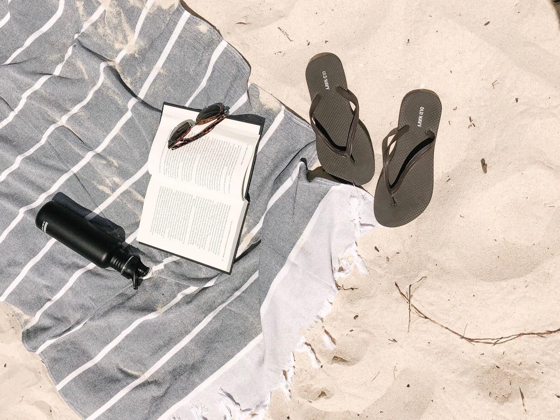 砂の上にあるサンダルと本