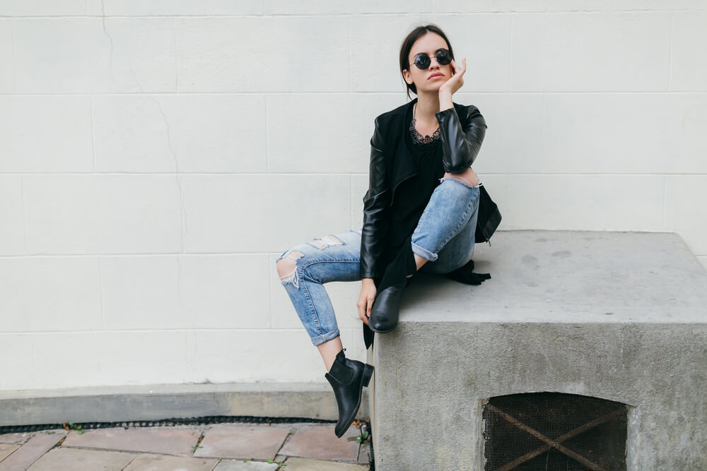 コンクリートの上に座るサングラスをかけた女性