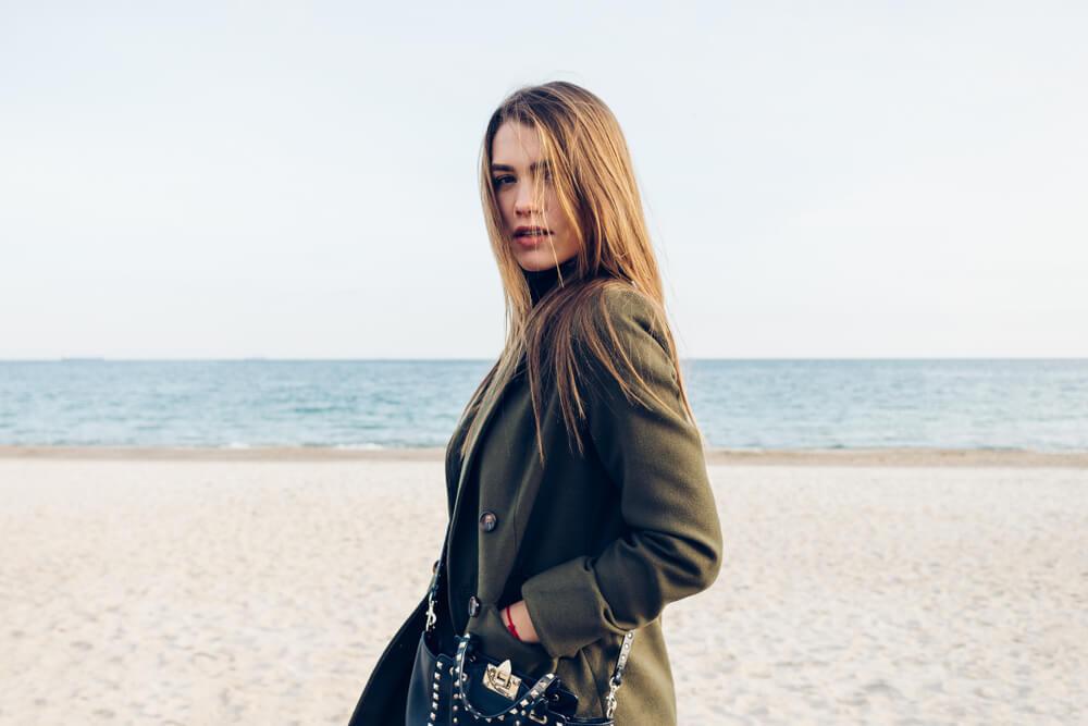 海辺に立つ黒いコートを着た女性