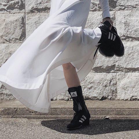 白いワンピースにブーツを履いた女性