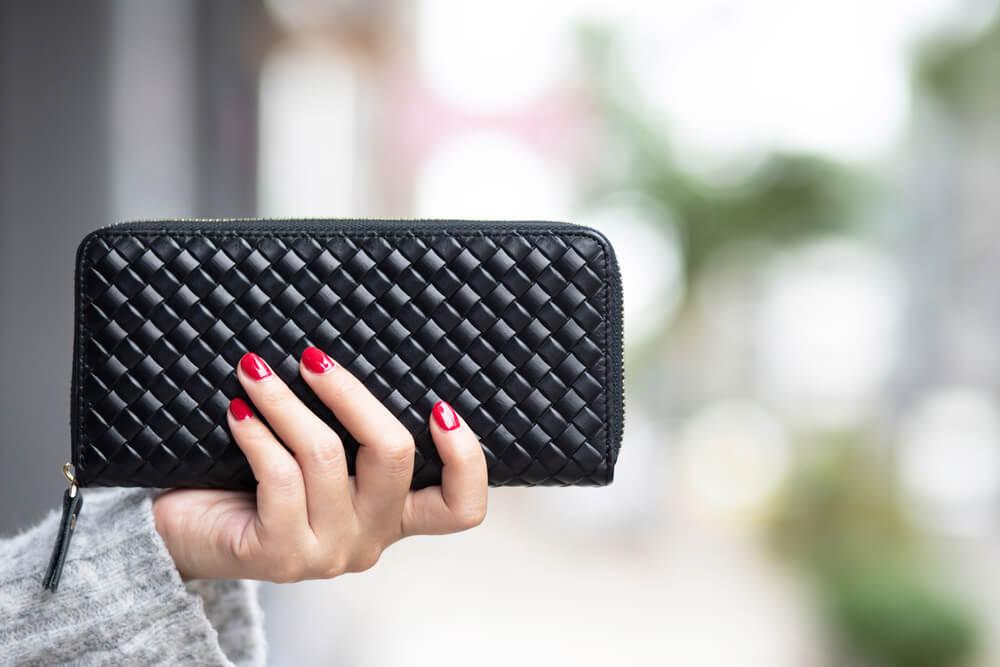 黒い財布を持つ女性