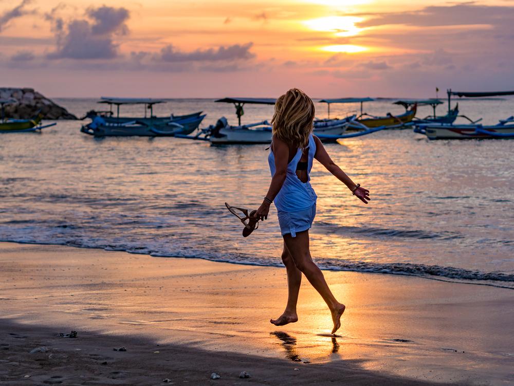 サンダル片手にバリのビーチを歩く女性