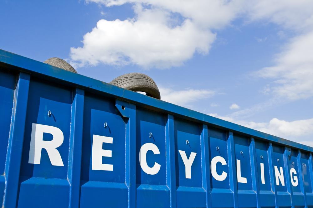 青い空背景のリサイクル車とタイヤ