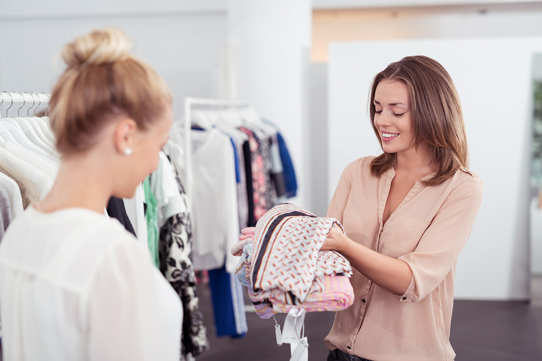 ショップで衣服を選ぶ女性