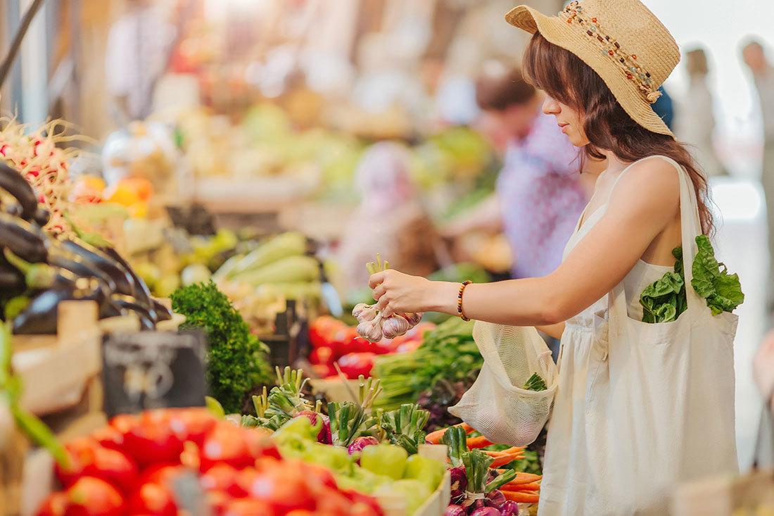 マイバッグ片手に野菜を選ぶ女性