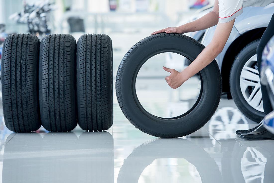 タイヤを持つ店員さんと4本のタイヤ