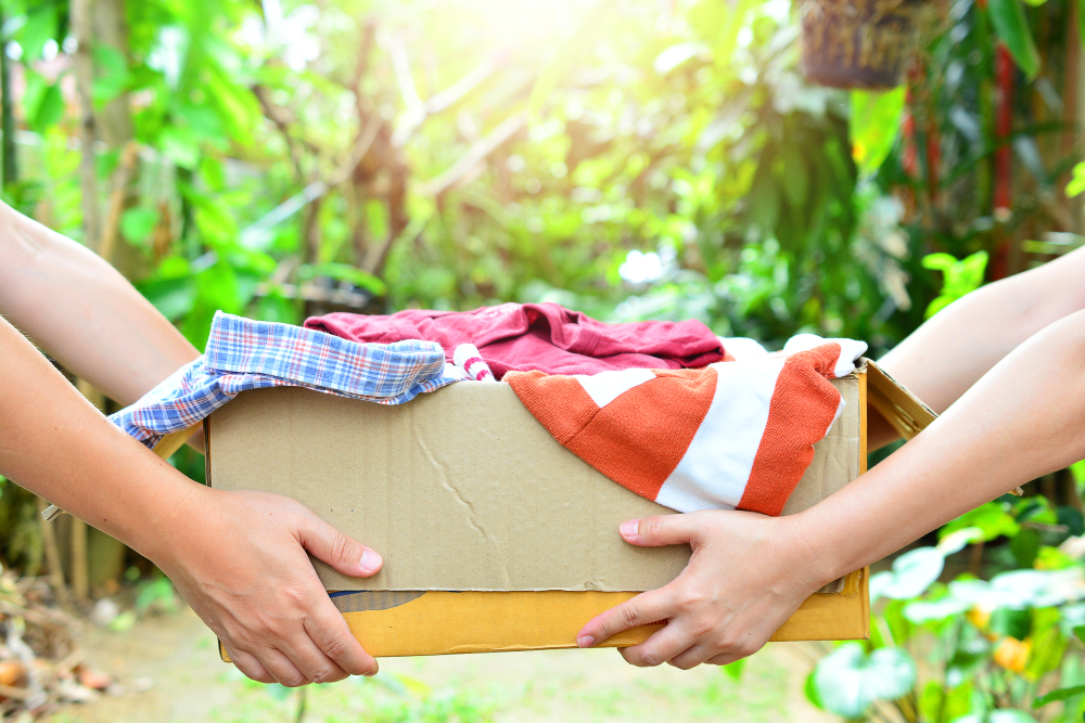 服が入った箱を渡す手