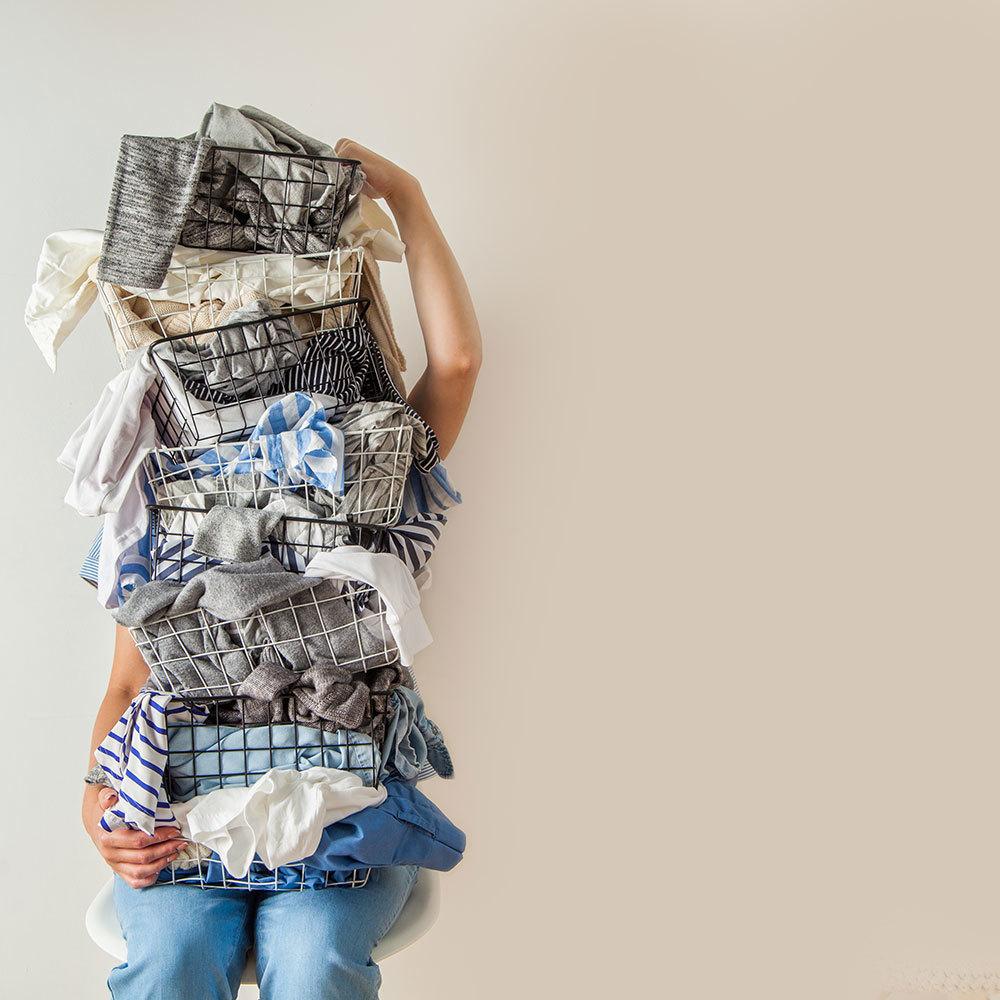 山積みの服を抱える女性