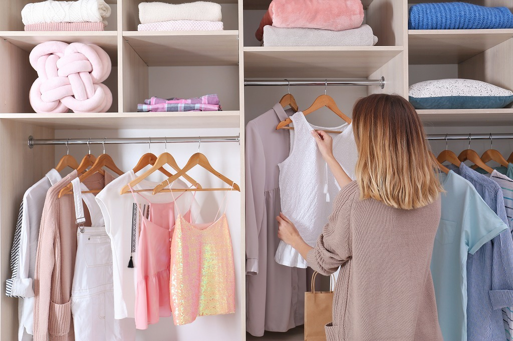 整頓されたクローゼットから衣装を選ぶ女性