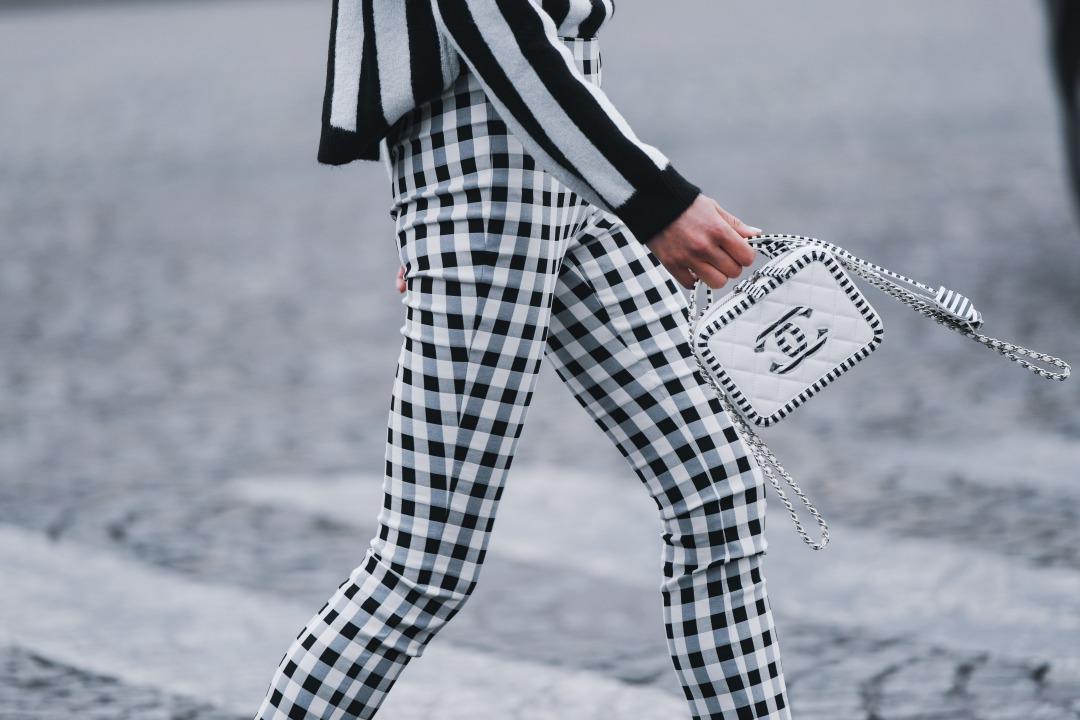 シャネルのバッグを持って歩く女性