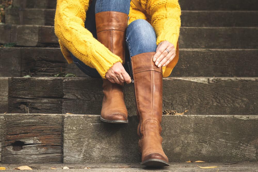 階段に座りブーツを履く女性