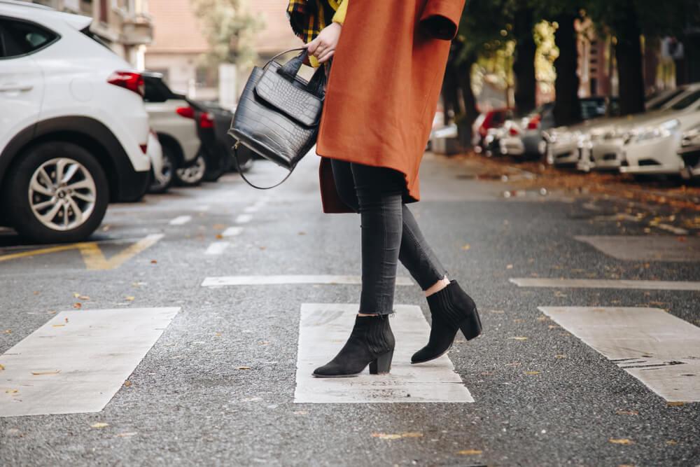 黒いブーツを履いて歩く女性