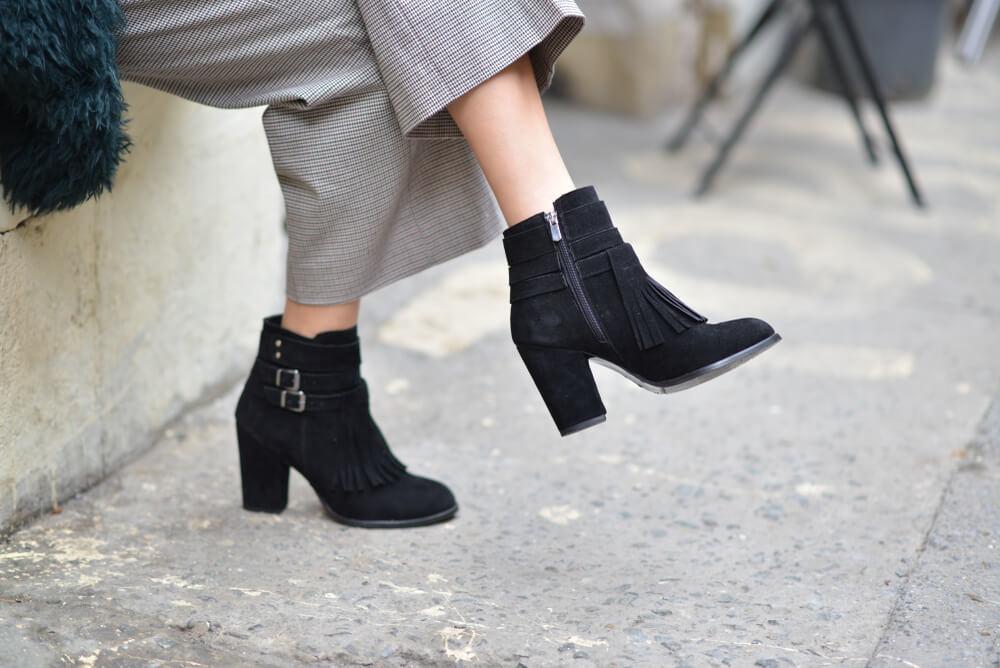 黒いスエードのブーツを履く女性