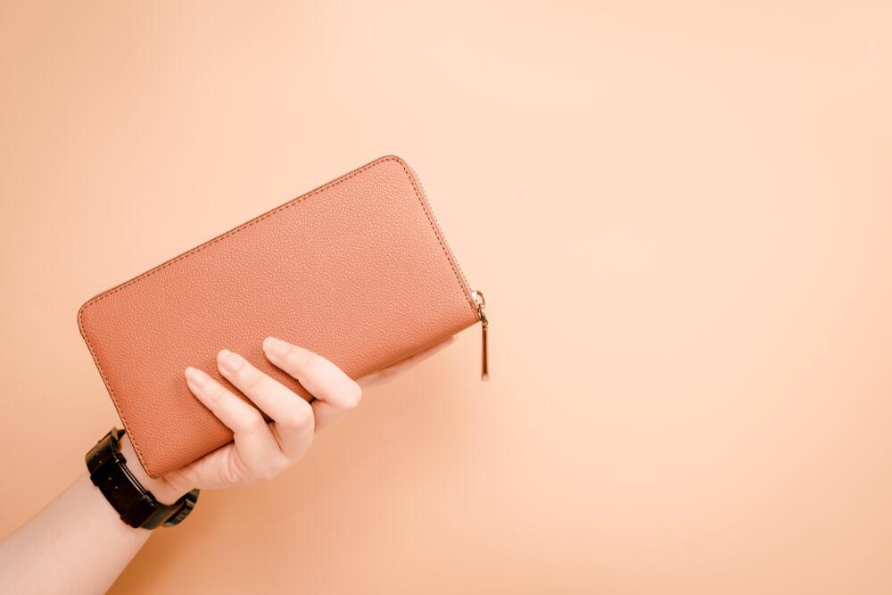ピンクの長財布を持つ女性の手