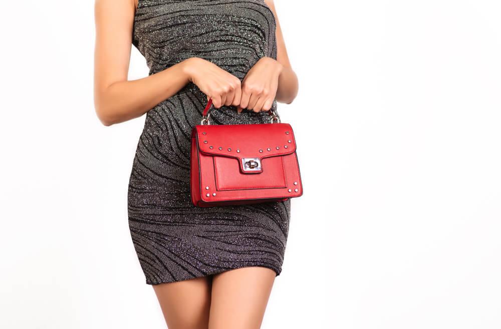 赤いバッグを両手で持つ女性