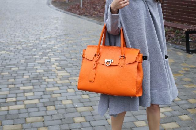 オレンジのハンドバッグを持つ女性