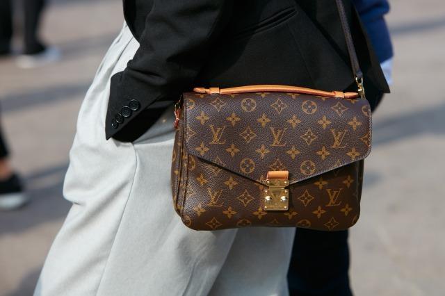 ルイヴィトンのショルダーバッグを持ってポケットに手を入れる女性