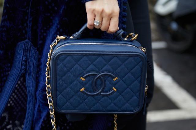 シャネルのブルーのショルダーバッグを持つ女性
