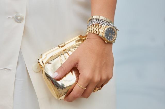 たくさんのジュエリーを身につけてゴールドの財布を持つ様子