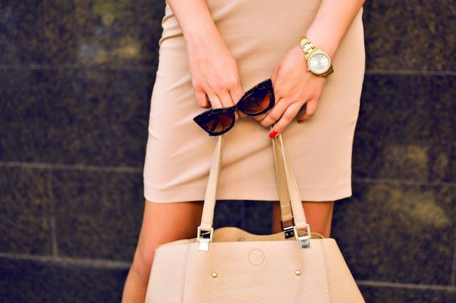バッグとサングラスを持つ女性