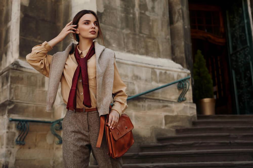 コンクリート壁の前のブラウン系ファッションで統一した美女